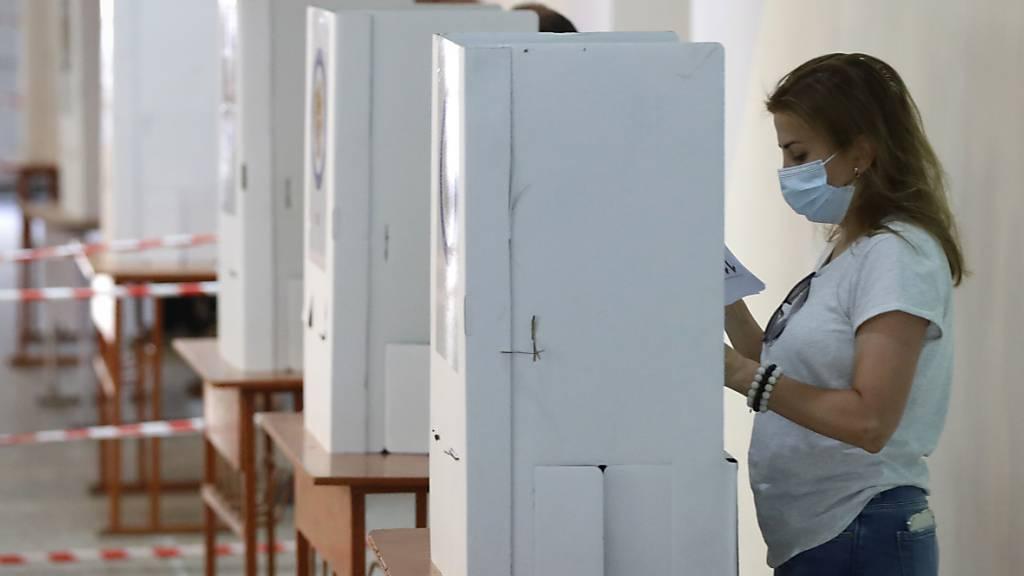 Menschen lesen während der Parlamentswahl in einem Wahllokal ihre Stimmzettel. Sieben Monate nach dem Krieg um die Konfliktregion Berg-Karabach wählt die krisengeschüttelte Südkaukasusrepublik Armenien ein neues Parlament. Foto: Sergei Grits/AP/dpa Foto: Sergei Grits/AP/dpa