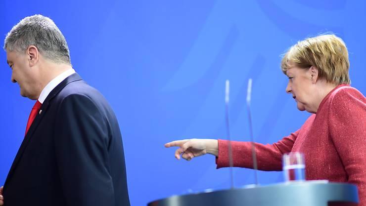 Dort geht's raus - so könnte es Umfragen zufolge für den ukrainischen Präsidenten bald aussehen. Demzufolge würde Herausforderer Selenskyj Poroschenko (links, bei Kanzlerin Merkel in Berlin) in der Stichwahl am Ostersonntag aus dem Amt jagen.