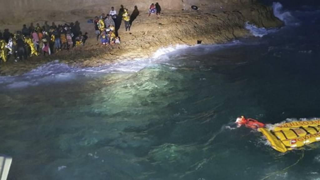 HANDOUT - Vor der Insel Lampedusa hat die italienische Küstenwache rund 125 Migranten gerettet. Die Menschen seien am Morgen wegen schlechter Wetterbedingungen an einem Riff festgesessen, teilte die Guardia Costiera am Donnerstag mit. Foto: Uncredited/Guardia Costiera/AP/dpa - ACHTUNG: Nur zur redaktionellen Verwendung und nur mit vollständiger Nennung des vorstehenden Credits