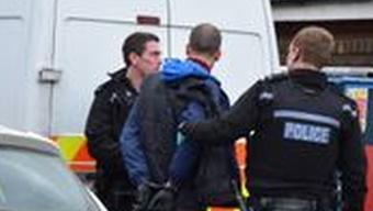 Polizisten nehmen einen Mann in Milton Keynes im Norden Londons fest.