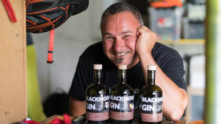Urs Riedo mit seinen Gin-Flaschen.