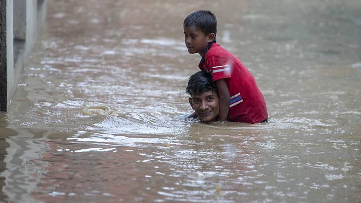 Ein Mann trägt seinen jüngeren Bruder durch eine überschwemmte Strasse in der nepalesischen Hauptstadt Kathmandu. (Archivbild)