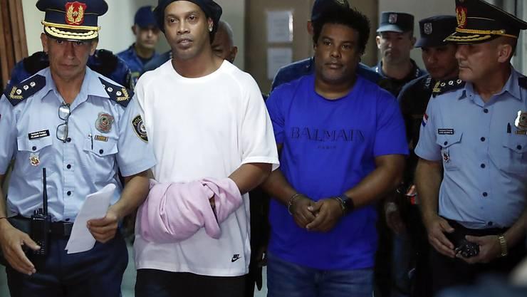 Muss weiter im Gefängnis sitzen: Ex-Fussballprofi Ronaldinho (zweiter von links) und sein Bruder  Roberto de Assis auf dem Weg zu einem Gerichtstermin.