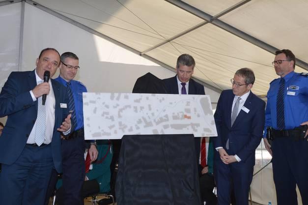 Zur Einweihung des neuen Polizeigebäudes in Frick haben die beiden Regierungsräte Markus Dieth (links mit Mikrofon) und Urs Hofmann (rechts) ein Geschenk mitgebracht. Es ist eine eine grosse Lagekarte, die im Foyer des Gebäudes aufgehängt wird.