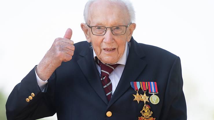 ARCHIV - Der damals 99-jährige Kriegsveteran Tom Moore zeigt seinen Daumen nach oben. Der inzwischen 100 Jahre alte Brite, der mit seinem Spendenlauf am Rollator einen Weltrekord aufgestellt hat, wird zum Ritter geschlagen. Foto: Joe Giddens/PA Wire/dpa