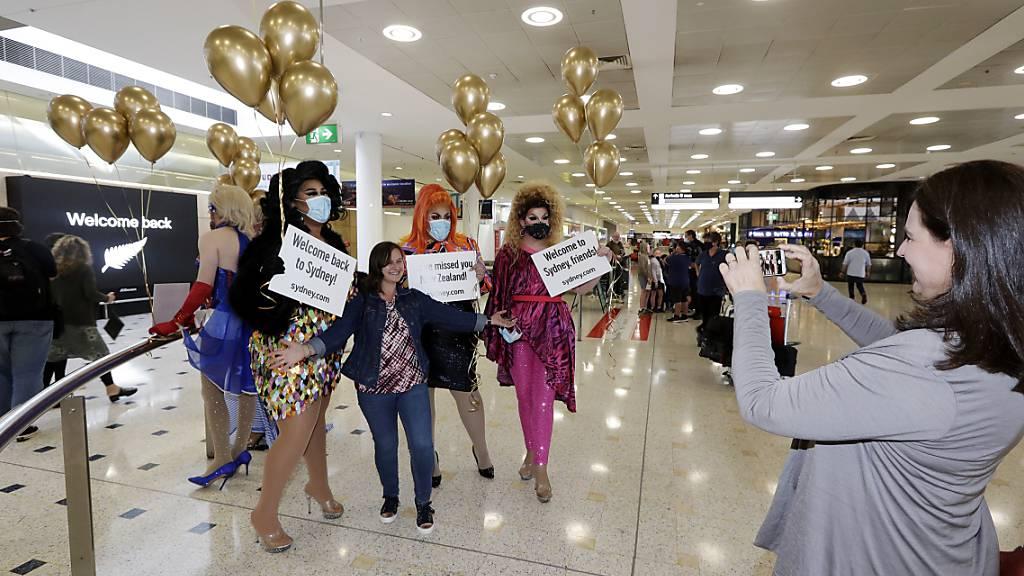 Eine Passagierin aus Neuseeland (M) stellt sich mit sich für ein Foto mit Drag Queens, die sie am Flughafen Sydney begrüßen, auf. Erstmals seit Beginn der Corona-Pandemie können Menschen in Neuseeland und Australien ab dem 19. April wieder zwischen beiden Ländern reisen. Foto: Rick Rycroft/AP/dpa