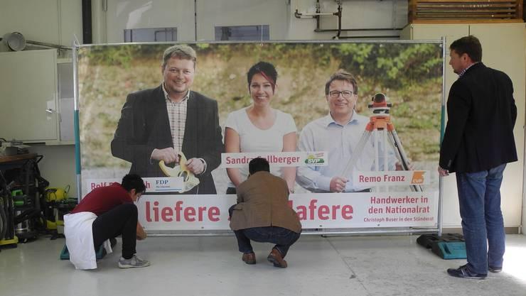 Sandra Sollberger, Remo Franz und Rolf Richterich legen gleich selber Hand an ihr Wahlplakat an.
