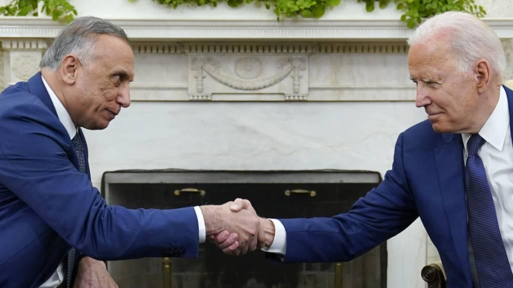 Joe Biden (r), Präsident der USA, schüttelt die Hand des irakischen Ministerpräsidenten Mustafa al-Kasimi im Oval Office des Weißen Hauses in Washington. Foto: Susan Walsh/AP/dpa
