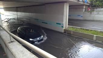Autos schwimmen durch die Unterführung Überlandstrasse in Dietikon.