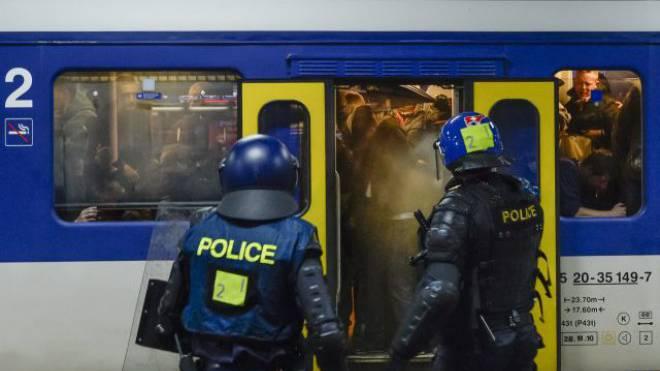 Polizisten in der Schweiz empfangen am Bahnhof einen Extrazug mit randalierenden Fans. Foto: JEAN-CHRISTOPHE BOTT/Keystone