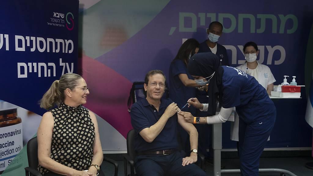 Izchak Herzog (M), Staatspräsident von Israel, erhält eine dritte Impfung gegen das Coronavirus, während seine Frau Michal (l) zusieht. Foto: Maya Alleruzzo/POOL AP/dpa