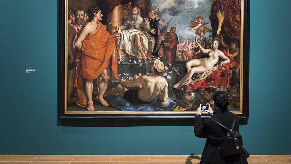"""Eine Besucherin fotografiert das Gemälde """"Allegorie mit Hermes, der Pandora dem König Epimetheus präsentiert"""" (1611) des niederländischen Malers Hendrick Goltzius in der Ausstellung """"Hola Prado!"""" im Kunstmuseum Basel."""