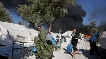 Die Flammen toben noch, als am Donnerstagmorgen Flüchtlinge ihre Habseligkeiten aus dem zerstörten Lager tragen.