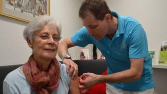 Arzt Beat Rickenbacher impft erstmals in der Kapuziner Apotheke in Rheinfelden eine Kundin gegen die Grippe.