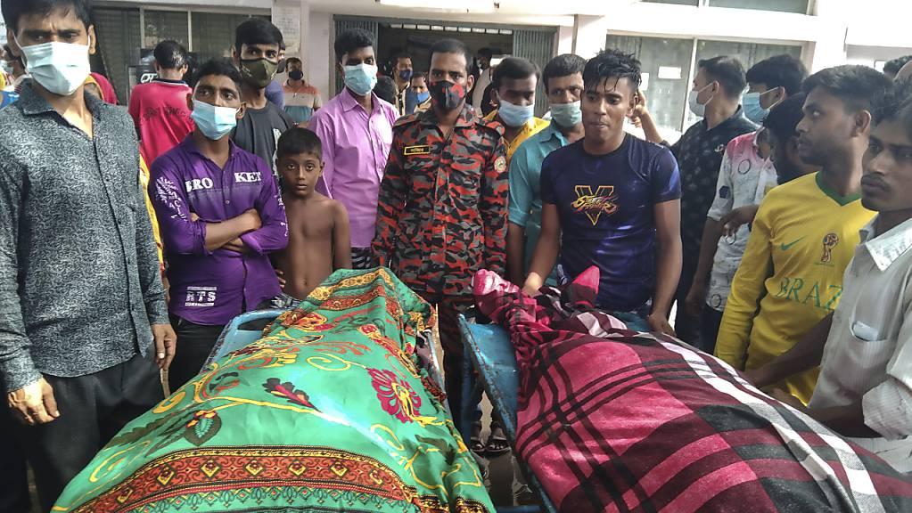 Personen stehen um die Leichen von Opfern, die durch einen Blitzeinschlag starben. Mindestens 15 Gäste sind auf dem Weg zu einer Hochzeitsfeier in Bangladesch vom Blitz getroffen worden und gestorben.