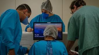 Medizinische Mitarbeiter arbeiten im öffentlichen Krankenhaus Parelheiros. Die Zahl der Corona-Toten in Brasilien liegt bei über 50 000. Foto: Lincon Zarbietti/dpa