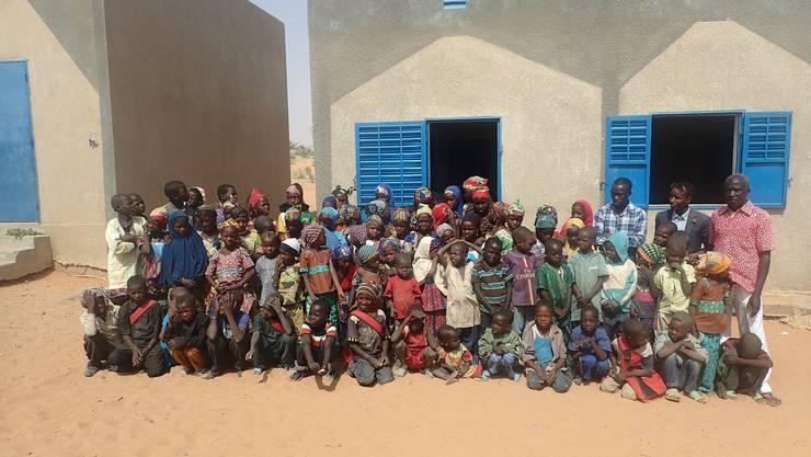 Alle Schülerinnen und Schüler sowie die drei Primarlehrer vor ihrer Schule in Bouara.