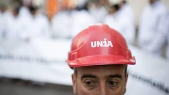 Ein Mitarbeiter der Gewerkschaft Unia demonstriert gegen Lohndumping bei der Gipserfirma Goger-Swiss auf der FIFA Baustelle, am Mittwoch, 8. April 2015, in Zürich.