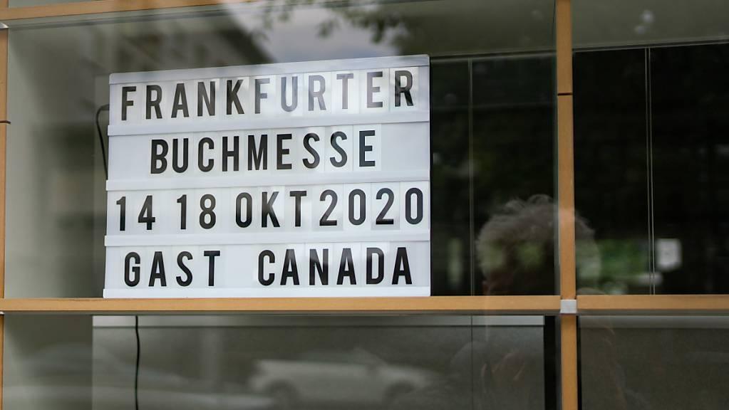 ARCHIV - Ein Schild mit dem Termin der diesjährigen Buchmesse steht in einem Fenster im Gebäude des Börsenvereins des Deutschen Buchhandels in der Frankfurter Braubachgasse. (zu dpa «Kanada verschiebt Ehrengast-Auftritt auf Buchmesse um ein Jahr») Foto: Frank Rumpenhorst/dpa