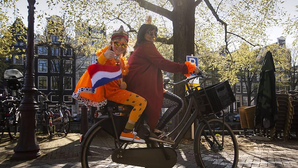 Eine Mutter und ihre Tochter, die ein orangefarbenes Königsgewand mit der niederländischen Flagge trägt, am Königstag in Amsterdam. Foto: Peter Dejong/AP/dpa
