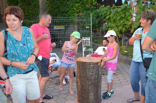 Treffsicher: Die Mädchen schlagen die Nägel in den Baumstrunk.