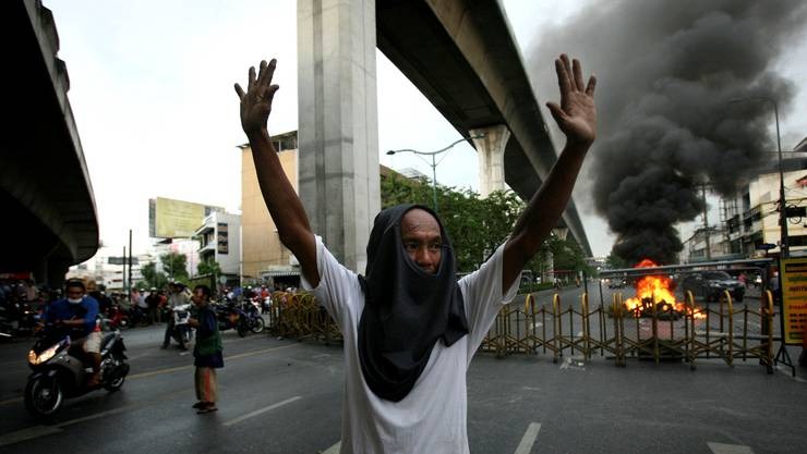 An anti-government protester tries to push back approaching police at the edge of Victory Monument intersection trying to disperse protesters and remove a fire road block, Monday, May 17, 2010 in Bangkok, Thailand. Thailand's Red Shirts offered peace talks Monday to end raging street battles in Bangkok as a government deadline demanding the demonstrators vacate a protest zone passed without capitulation. (AP Photo/Wally Santana)