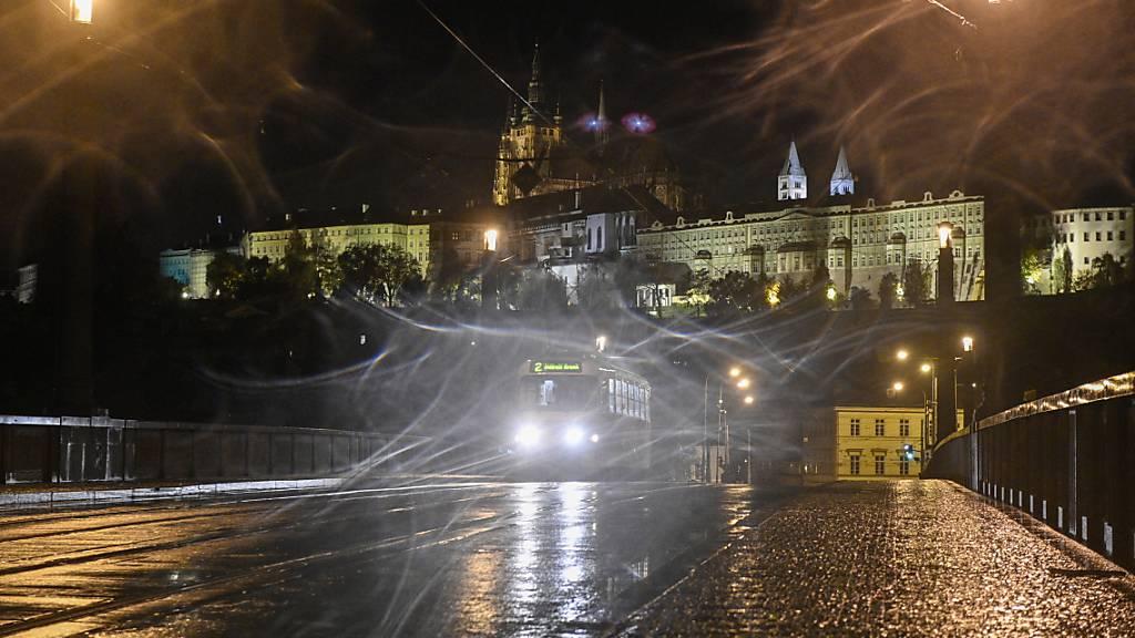 Ein Strassenbahn fährt über eine leere Strasse in Prag während einer nächtlichen Ausgangssperre aufgrund einer Corona-Pandemie. Im Hintergrund die Prager Burg. Foto: Michal Kamaryt/CTK/dpa