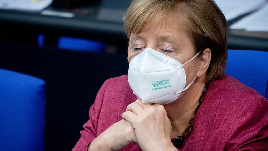 Bundeskanzlerin Angela Merkel (CDU) verfolgt mit geschlossenen Augen und Mund-Nasenbedeckung die Sitzung des Bundestages. Sie hatte vorher eine Regierungserklärung zur Bewältigung der Corona-Pandemie abgegeben. Foto: Kay Nietfeld/dpa