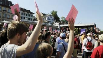 Passantinnen und Passanten strecken Wahlzettel in die Höhe, anlaesslich einer Landsgemeinde auf der Rathausbruecke, 2011, in Zuerich.