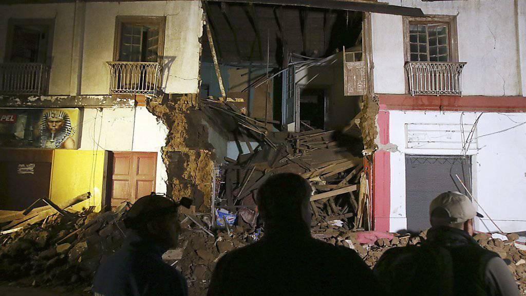 Chilenen vor einem eingestürzten Gebäude in Illapel