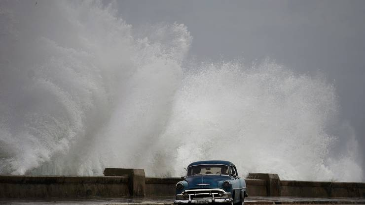 Waves crash against the Malecon, triggered by the outer bands of Hurricane Michael, as man drives past in a classic American car in Havana, Cuba, Tuesday, Oct. 9, 2018. A fast and furious Hurricane Michael is churning toward the Florida Panhandle with 110 mph winds and a potential storm surge of 12 feet, giving tens of thousands of people precious little time to get out. (AP Photo/Ramon Espinosa