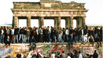 Am Tag nach der Öffnung am 9. Nov. 1989 steigen Menschen am 10. Nov. 1989 auf die Berliner Mauer vor dem Brandenburger Tor in Berlin. Wie kaum ein anderes Datum steht der 9. November für die Irrungen und Wirrungen der deutschen Geschichte.