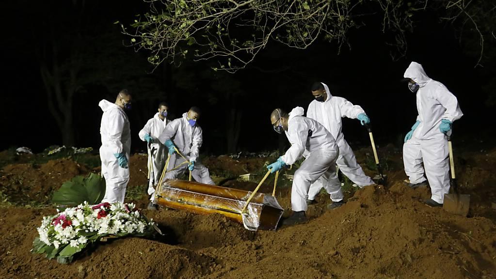Friedhofsarbeiter senken den Sarg eines Covid-19-Opfers in sein Grab auf dem Friedhof Vila Formosa. Foto: Nelson Antoine/AP/dpa