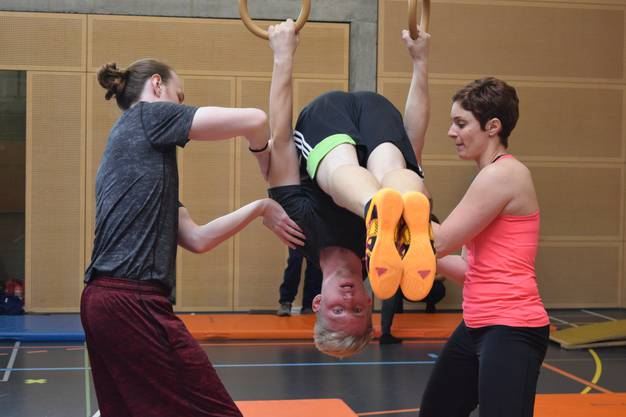 """Wie sichert man jemanden, der an den Ringen hängt? Das lernten die Teilnehmer des """"Jump In""""-Kurses des Solothurner Turnverbandes von Co-Leiterin Nadine Pfluger (rechts im Bild)."""