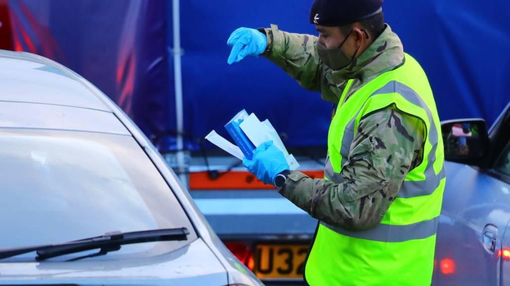 Ein Mann führt einen Corona-Test bei einer im Auto sitzenden Person am Hafen von Dover durch. Die britische-französisch Grenze soll über die Weihnachtsfeiertage offen bleiben und der Verkehr durch den Eurotunnel soll weitergehen. Foto: Aaron Chown/PA Wire/dpa