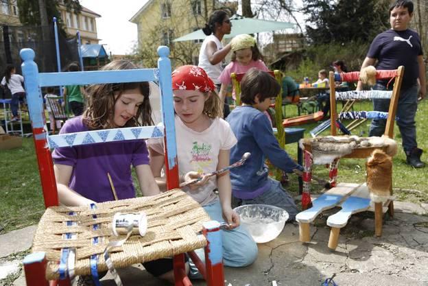 Mit Farbe und verschiedenen Materialien sind die Kinder am Werk.