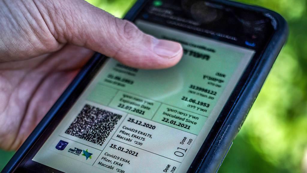 Ein israelischer Mann hält ein Smartphone in der Hand, auf dem der sogenannte «Grüne Pass» abgebildet ist. Angesichts stark ansteigender Corona-Infektionszahlen dehnt Israel die Anwendung des sogenannten Grünen Passes auf fast alle Bereiche des öffentlichen Lebens aus.
