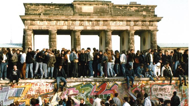 Am Tag nach der Öffnungen steigen Menschen auf die Berliner Mauer vor dem Brandenburger Tor in Berlin.