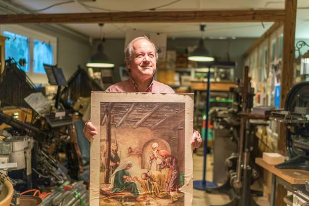Stolz präsentiert Bruno Altherr das Bild, das von der alten Steindruckpresse gedruckt worden ist.