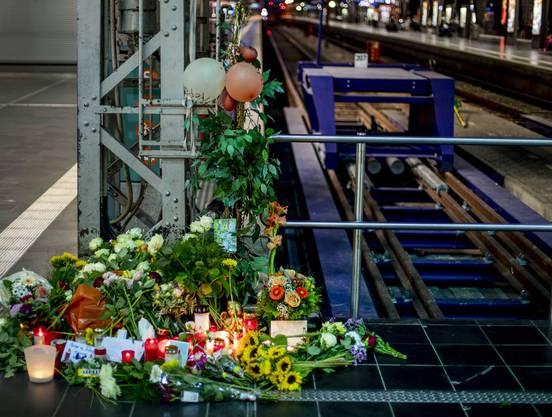 Blumen und Kerzen in der Nähe des Tatorts.