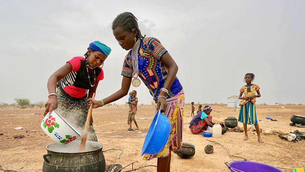 Frauen bereiten im Norden des Landes auf einem offenen Feuer in einem grossen Topf eine Mahlzeit zu.