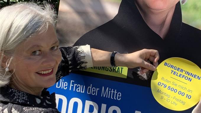 Die doppelte Regierungsrats-Kandidatin: Doris Aebi bringt einen Kleber für ihre Telefonaktion auf einem Wahlplakat an. Bild: ZVG