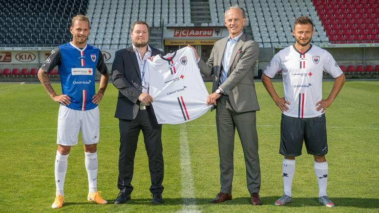 Philipp Bonorand, Präsident FC Aarau, und Roberto Belci, Chef der CS-Region Aargau, präsentieren mit den FCA-Spielern Olivier Jäckle und Elsad Zverotic das neue Trikot.