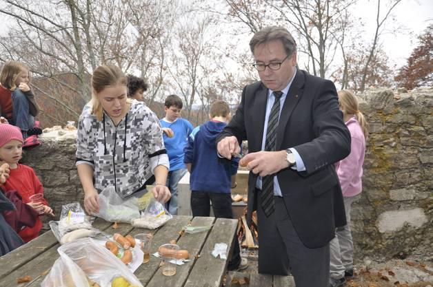 Regierungsrat Urs Wüthrich hilft den Primarschülern beim Cervelatbräteln