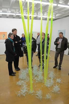 """Besucher bestaunen """"Para-Topie"""" von Andrina Jörg. Die asiatisch anmutende Skulptur besteht aus Plastikbechern. Für die  """"Blüten"""" am Boden wurde Plastikbesteck verwendet."""