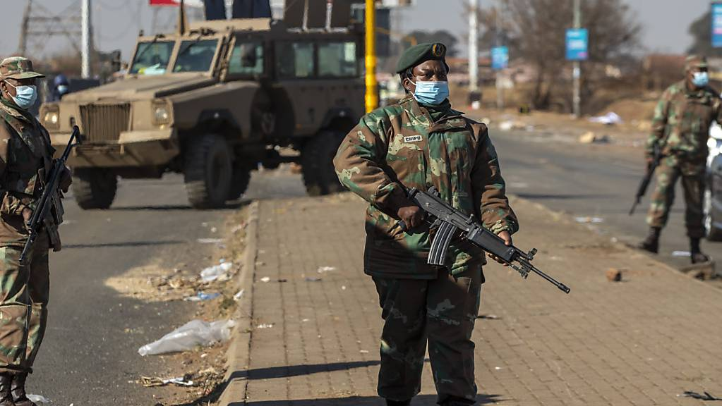 Bewaffnete Soldaten patrouillieren ausserhalb eines Einkaufszentrums. In Südafrika setzten sich die tagelangen gewalttätigen Proteste fort.