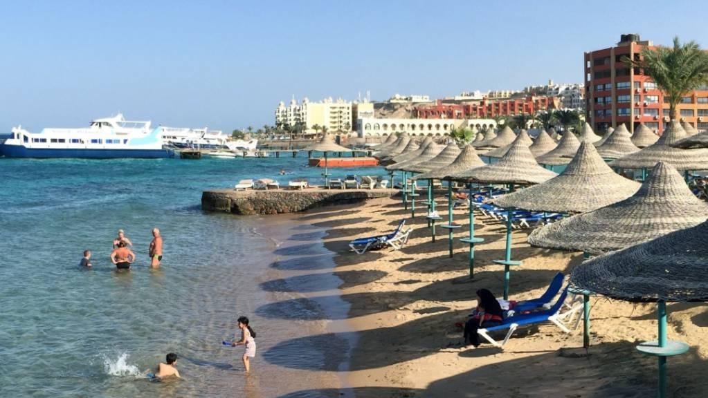 Touristen stehen im Wasser an einem Hotel-Strand.