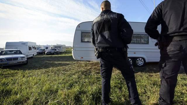 Polizisten beobachten eine Wagenkolonne von Fahrenden (Archiv)