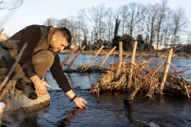 Ramiz Niksic setzt für den Fischerverein Kloster Fahr junge Bachorellen in die Limmat ein.