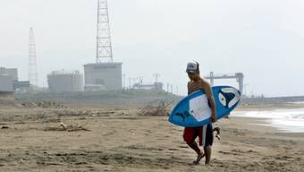 Ein Surfer vor einem Atomreaktor in Kashiwazaki (Archiv))